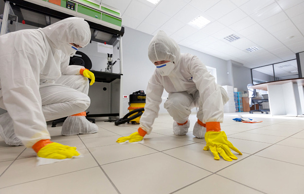 two people on COVID suit cleaning a floor